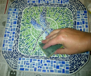 Using a wet sponge wipe off the excess grout.